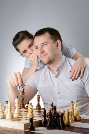 A man in a white shirt listening tips how to play chess