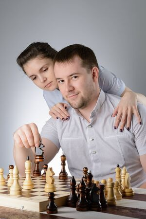 Woman standing behind and watching men playing chess