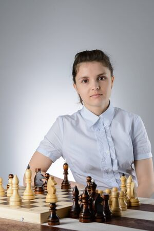 pawn to king: Business woman in a light blue shirt, playing chess