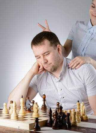 pawn adult: Woman in white shirt standing behind the man and put him horns Stock Photo