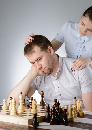 pawn adult: Woman in white shirt standing behind the men and pats him on the head