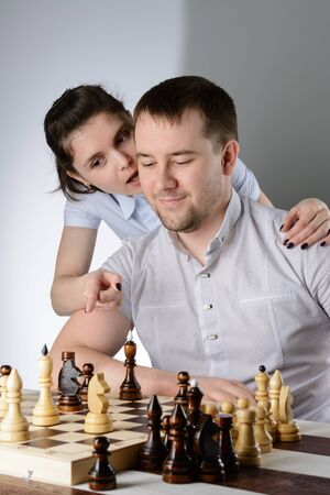 The woman tells the man's ear how to play chess Imagens