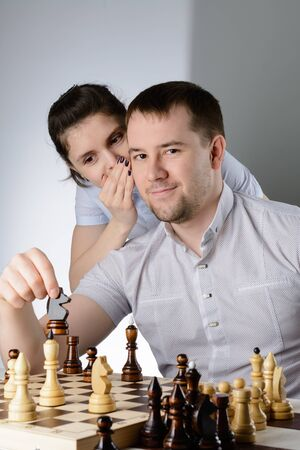 The woman tells the man's ear how to play chess