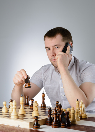 pawn adult: A man in a white shirt and thinks with the phone over a game of chess