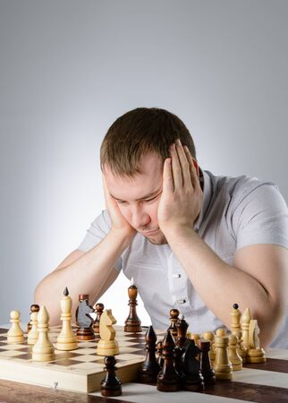 pawn adult: Man in white shirt thinking of the game of chess