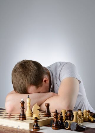 pawn adult: The man put his head on his folded hands on the chessboard