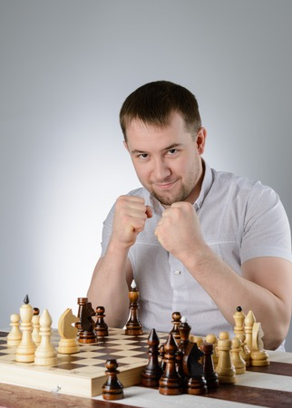 pawn adult: A man in a white shirt, clasped his hands in a fist on chess