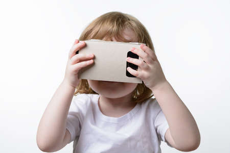 simulations: A child playing a virtual reality glasses Google Cardboard Stock Photo
