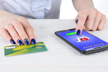 enters: A woman enters credit card details in the smart phone on a white table