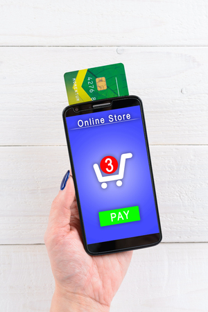 pay for: A woman holds a smartphone and pay for goods in the online store