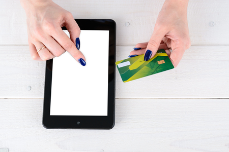 enters: A woman enters credit card details a tablet PC on white table Stock Photo