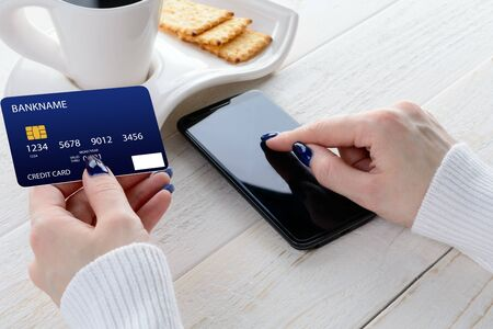 pay for: A woman sitting at a white wooden table and pay for purchases via smartphone