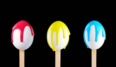 drench: White eggs on a wooden stick doused with paint Stock Photo