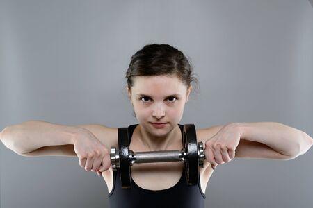 ropa deportiva: La mujer joven en ropa deportiva levantamiento pesas pesadas