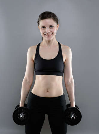 violence in sports: Young woman in sportswear lifting heavy dumbbells Stock Photo