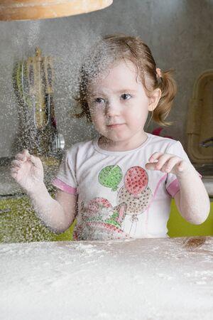 little dough: Little girl sifts the flour for the dough