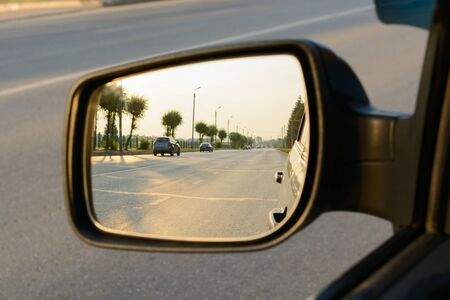 Reflection of a city street in the rearview mirror of car
