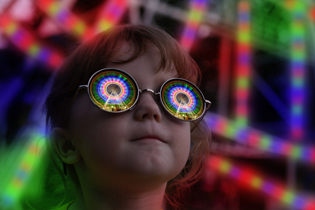 The little girl with glasses rides reflected in night illumination Banco de Imagens