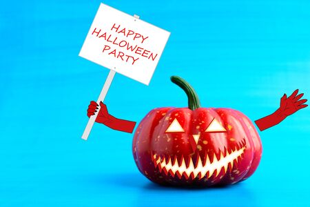 Halloween pumpkin with a poster in his hand on a blue background Stock Photo