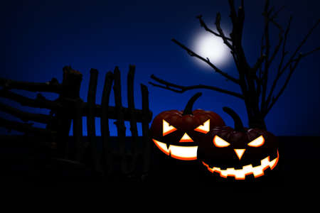 moon gate: Two Halloween pumpkin with scary face beside an old wooden fence