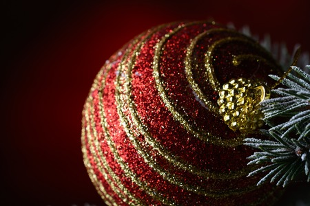 Christmas ball hanging on a fir branch on a dark red background