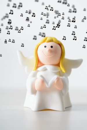 Toy angel with a book singing Christmas songs on a white background