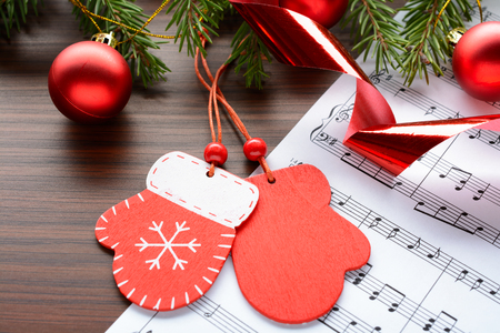 Christmas decorations and fir branch lying on notes sheet