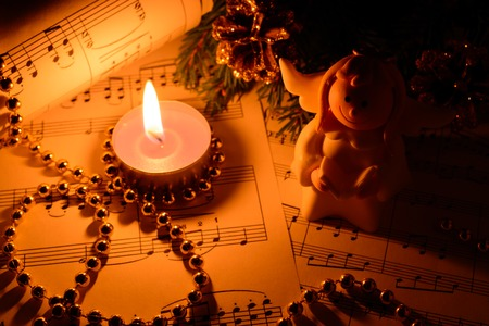 Christmas decorations, candles, figures of angels and notes in the dark Stock Photo