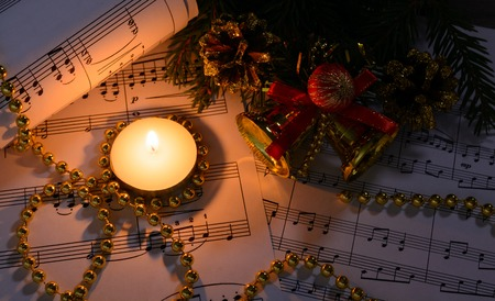 Christmas decorations, burning candle and sheet music in the dark