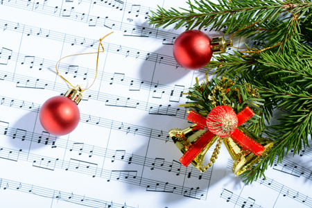 christmas carols: Christmas decorations and fir branch lying on notes sheet