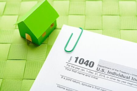 Paper house and tax form on a green wicker mat Banco de Imagens