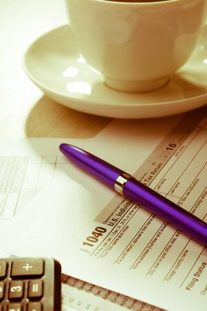A cup of coffee and tax form on the table