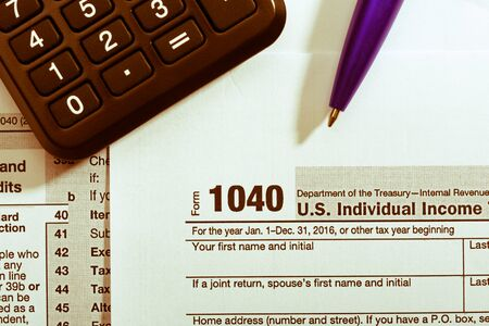 blue pen: Blue pen and calculator on tax form Stock Photo