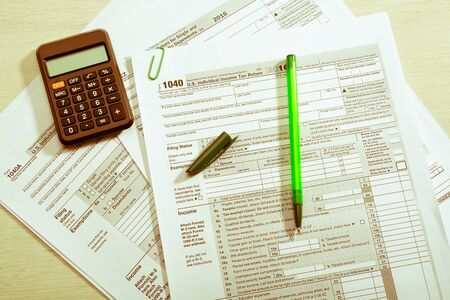 sepia toning: Green pen with cap and calculator on tax form Stock Photo