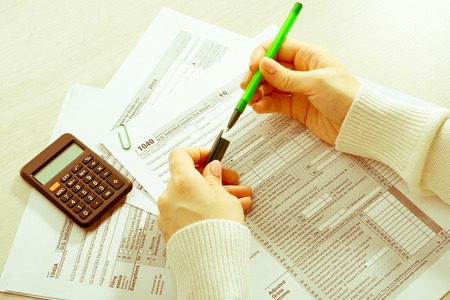 A woman sitting at a table and fills the tax form Stock Photo