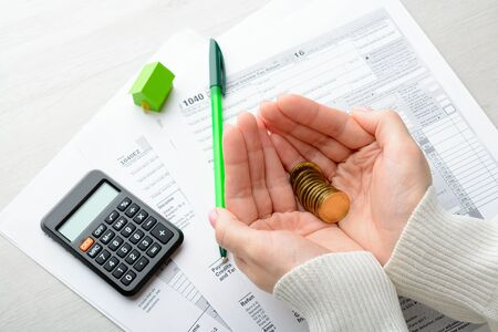 female form: Coins in female palms and tax form on the table Stock Photo