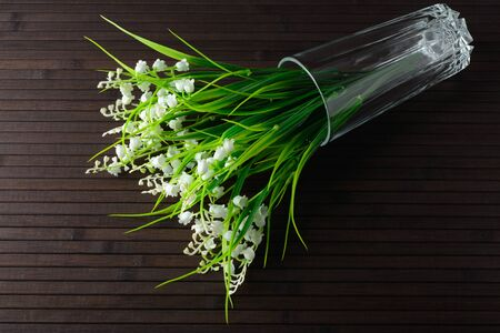 Bouquet of artificial lily in a glass on a bamboo background