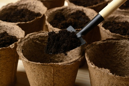Peat pots with soil and a spade on a wooden table Stock Photo