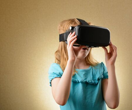 Little girl playing in virtual goggles indoors Stock Photo