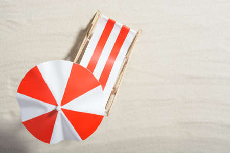 Red and white sunbed on the beach: top view