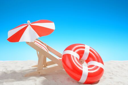 Deckchair and swimming ring on the beach on background of blue sky