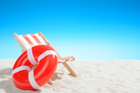 longue: Deckchair and swimming ring on the beach on background of blue sky