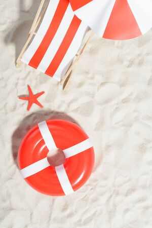 longue: Red and white deckchair and swimming ring on the beach: top view
