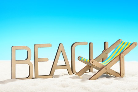 The word BEACH and sunbed at the beach on background of blue sky