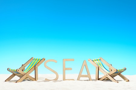 The word SEA and two sunbeds at the beach on background of blue sky