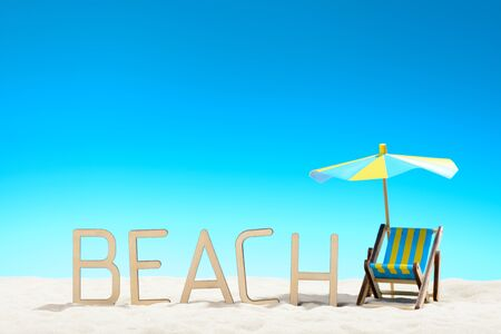 The word BEACH and two sunbeds at the beach on background of blue sky