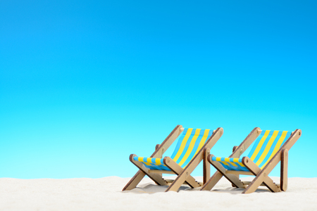 Two sunbeds at the beach on background of blue sky