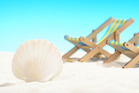 Seashell and two sunbeds at the beach on background of blue sky