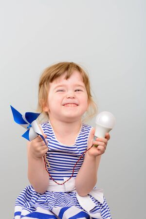 power cables: The concept of renewable energy. Cute girl with led light bulb and windmill