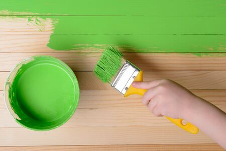 Childs hand with a brush paints wooden slats in green: top view